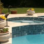 built-in hot tub with pool in backyard