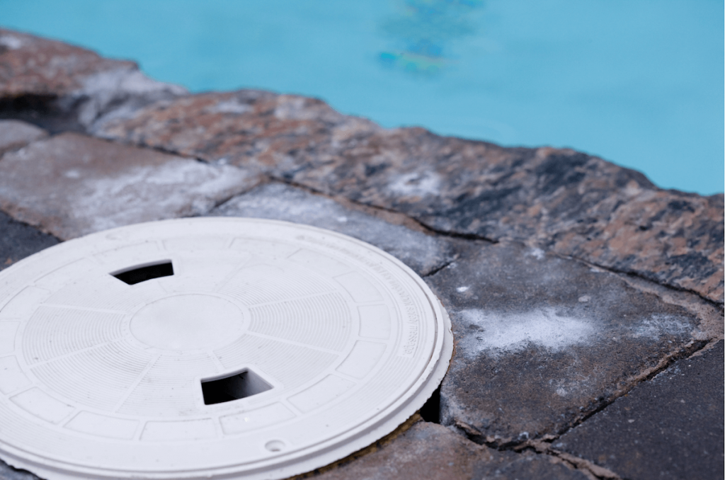 pool skimmer cover in stone pool surround