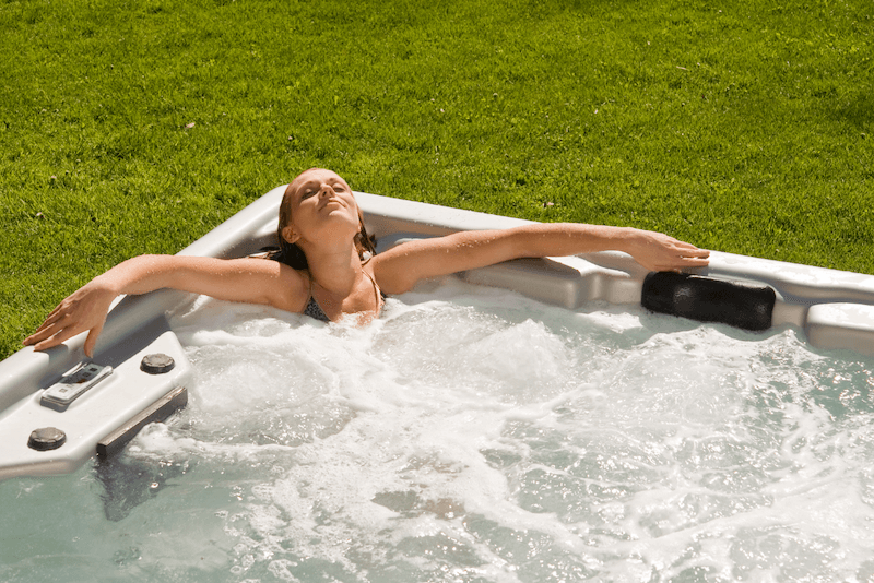 woman relaxing in clean, balanced hot tub or spa